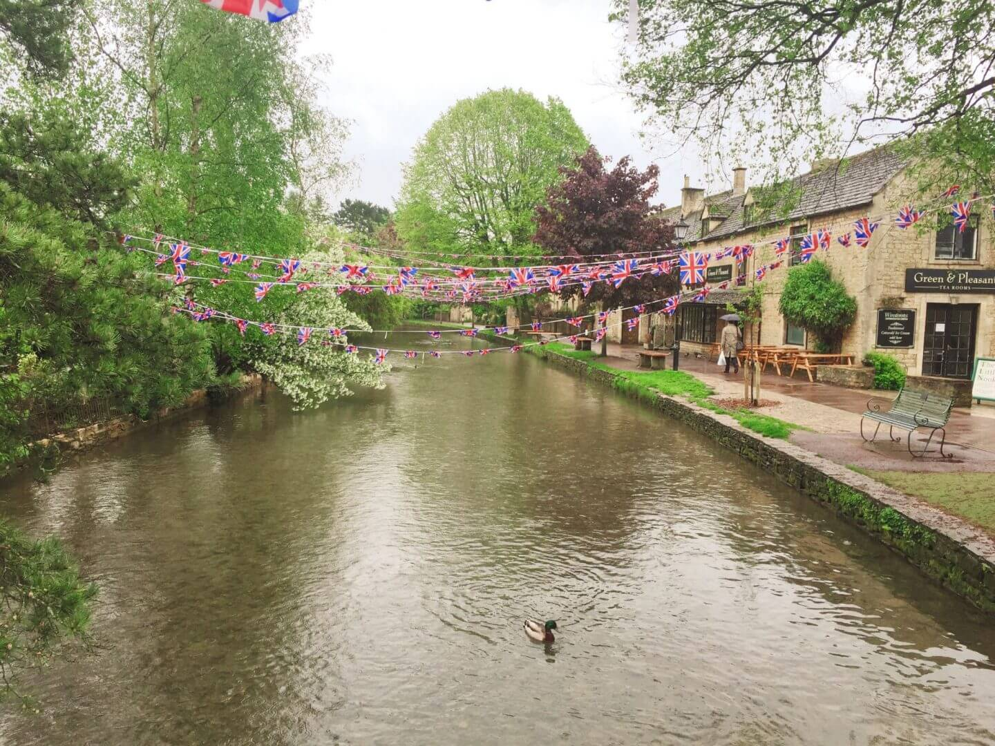 a stream running through the middle of Bourton-on-the-water, with Union Jack Bunting having over. Perfect scenes for a weekend trip to the Cotswolds