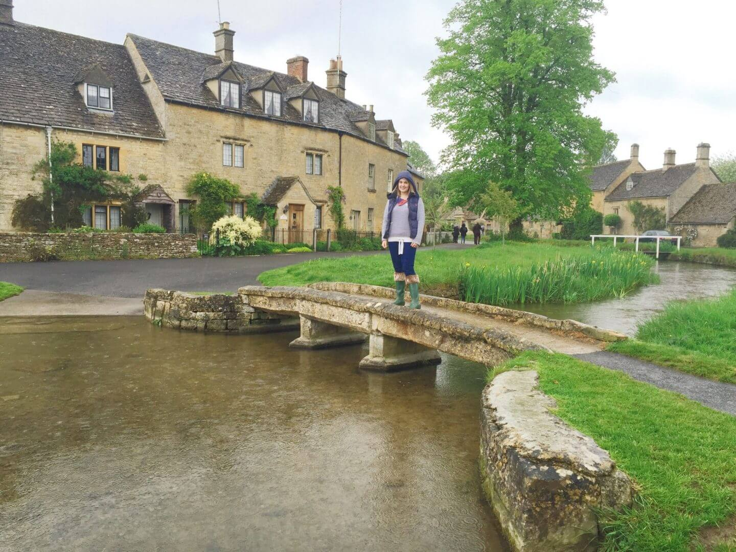 a bridge over a stream in Lower Slaughter, with yellow stone houses behind.