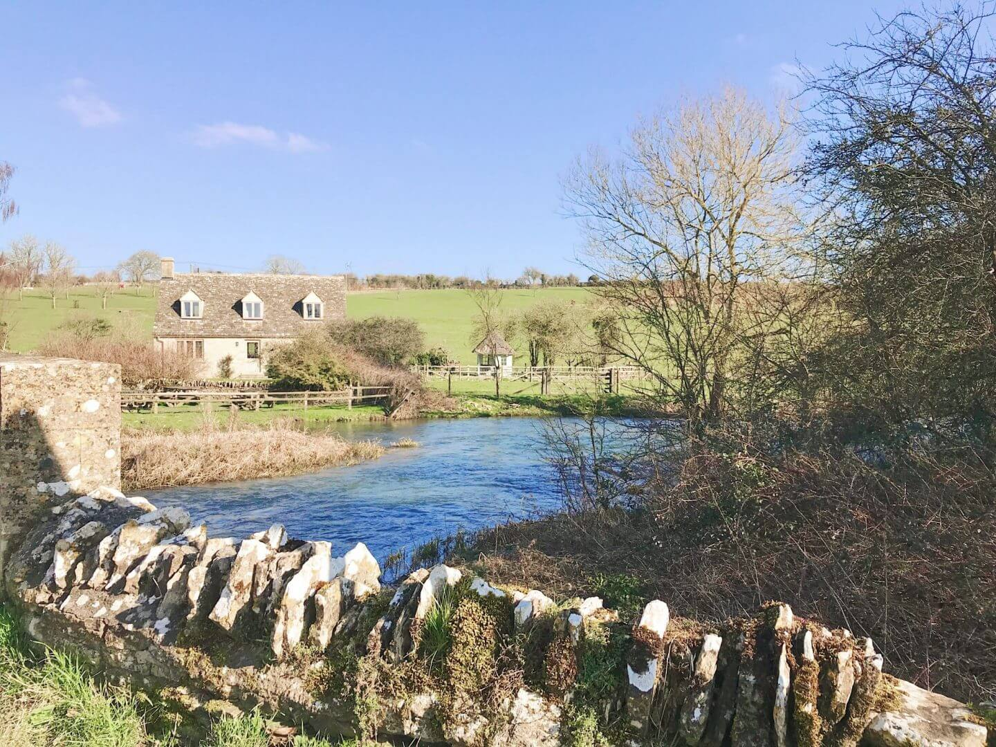 Stone walls and a stone house in a field, with a stream running by