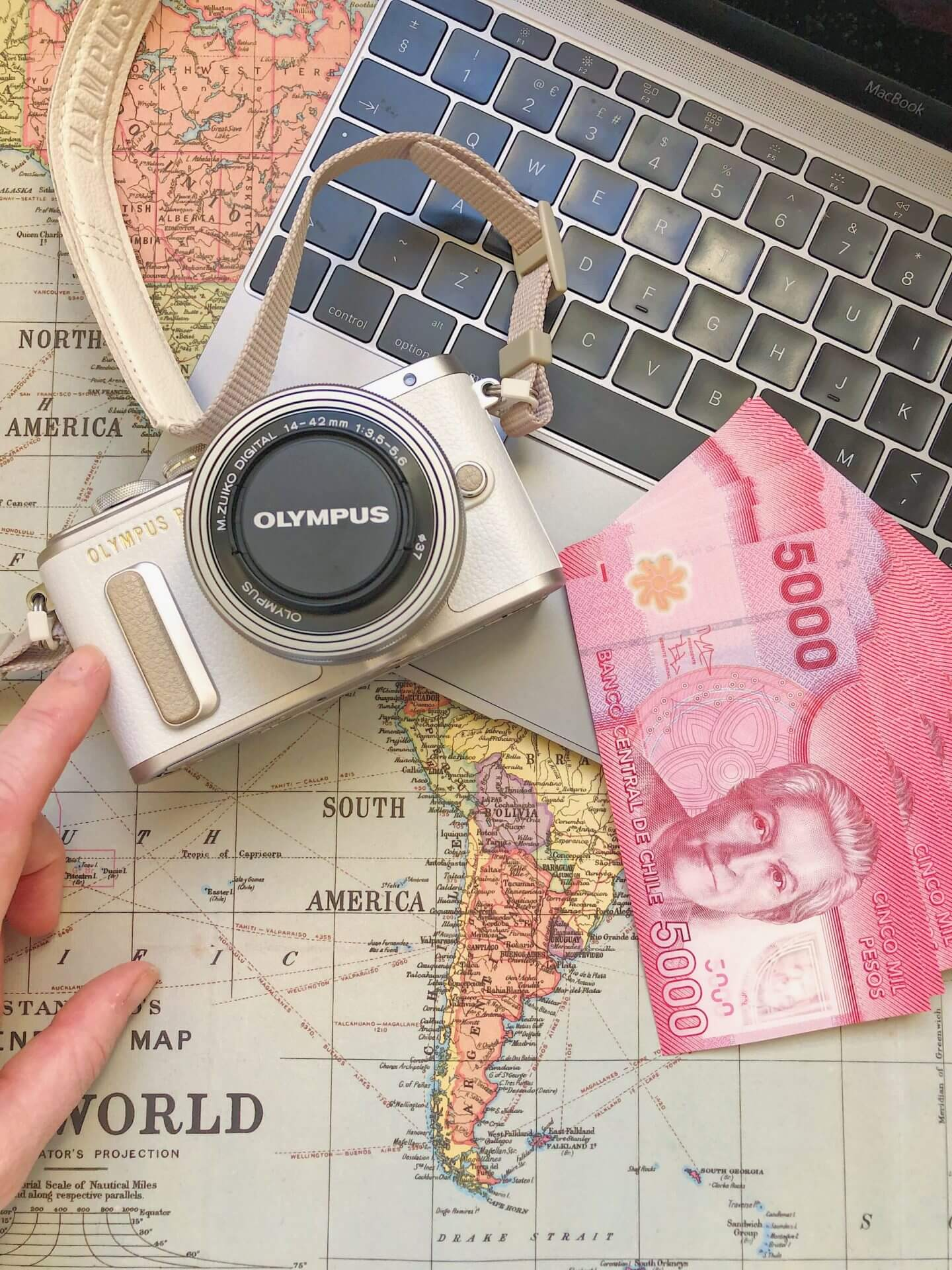 Image of packing essentials on world map - a camera, laptop and currency