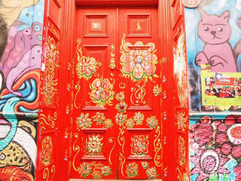 A red painted door, with yellow and green flowers, surrounded by blue and pink street art paintings