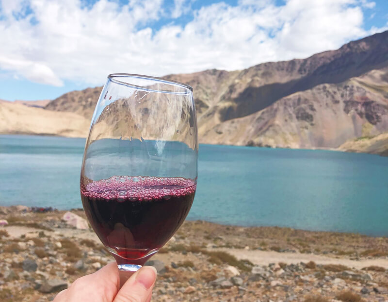 a glass of chilean red wine against a backdrop of deep blue glacier lake - a must for one week in Chile