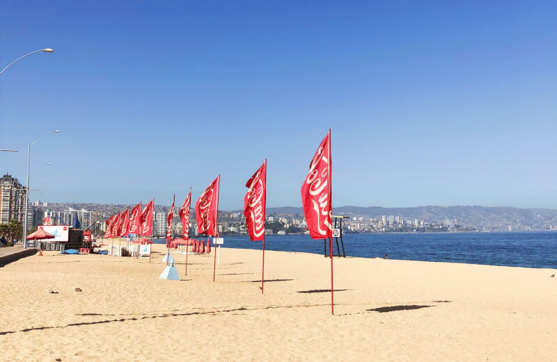 view along the beach in Vina Del Mar with red flags, golden sand and bright blue skies