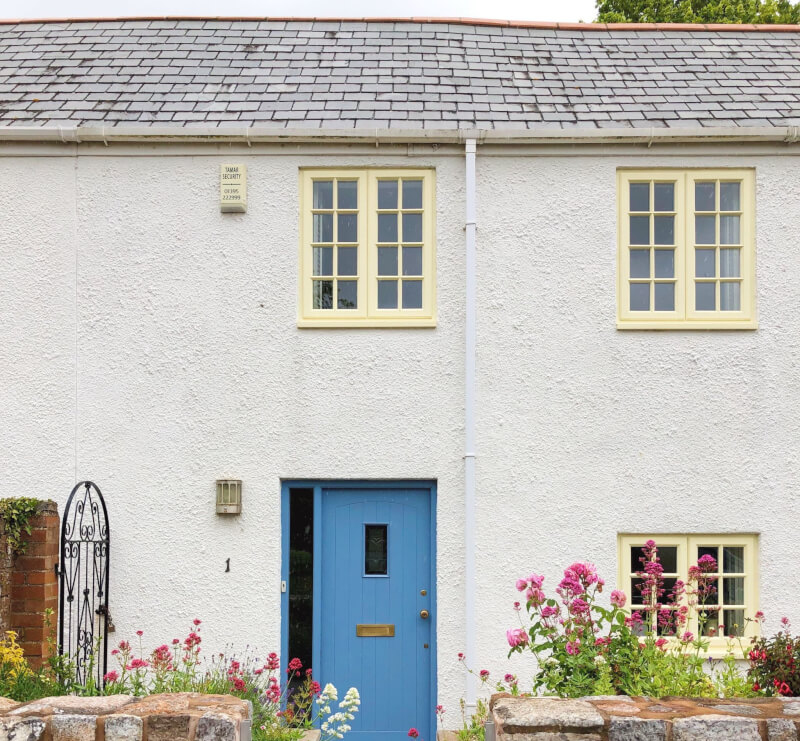 White House with blue door and yellow windows in Devon