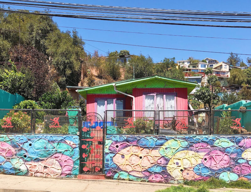a pink and green house on a residential street in Valparaiso in front of art of painted coloured fish