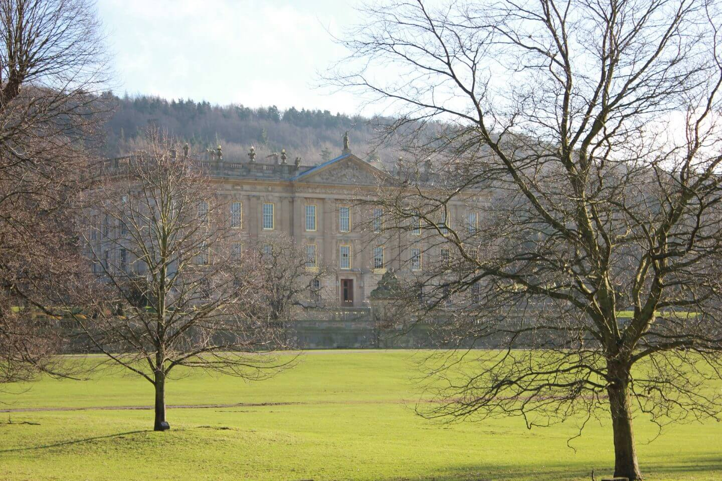 The beautiful Chatsworth House peeking through bare trees against a sunny sky