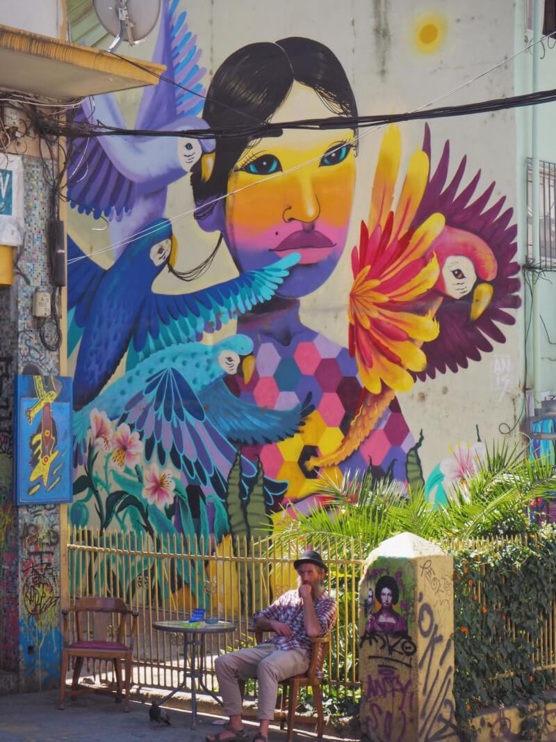 Brightly coloured mural of a woman with a man sitting below