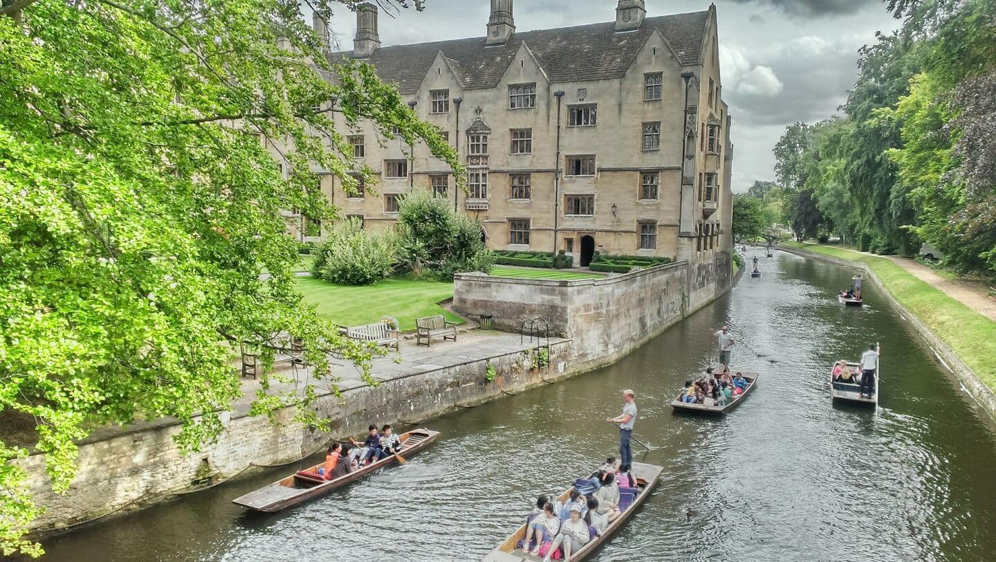 Punting in Cambridge with old buildings and green trees making it one of the best weekend trips in the UK