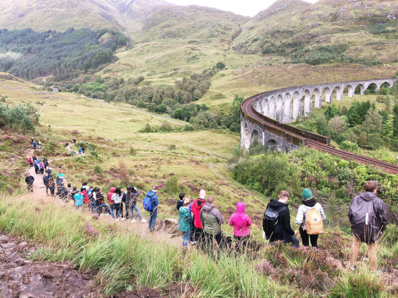 image of people standing on the path at the Glenfinnan Viaduct Viewpoint looking towards the bridge