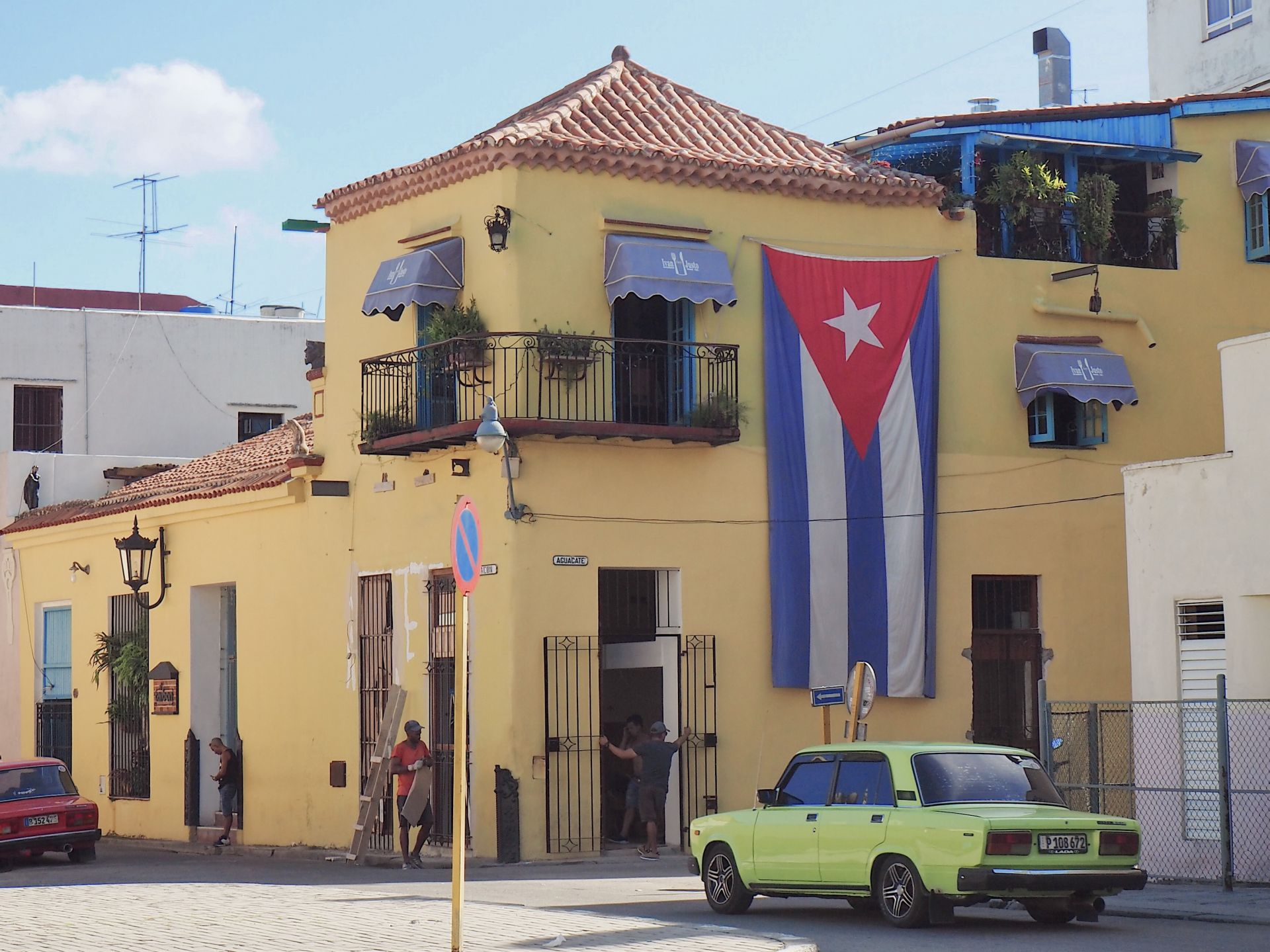 Image of Cuban flag against a yellow house in Havana