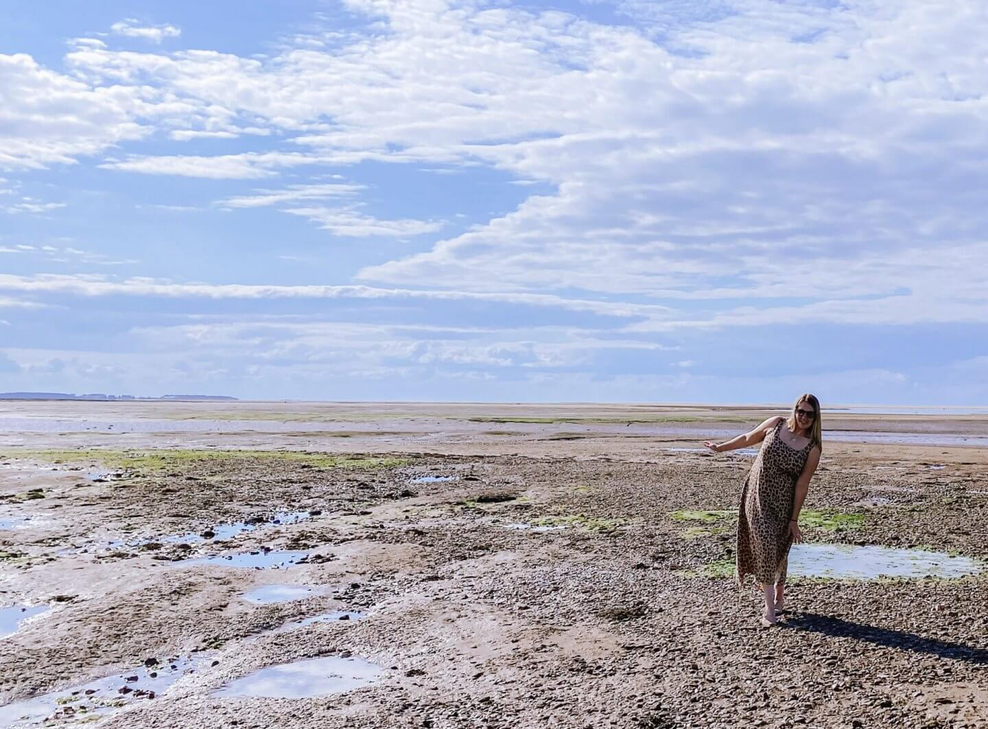image of woman standing on mud flats in Cley, North Norfolk